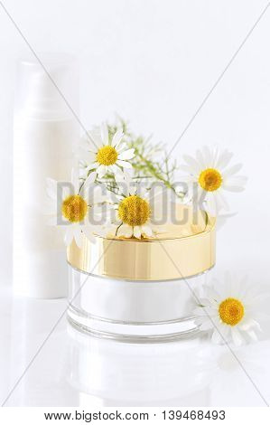 chamomile and jars of cream on the white background