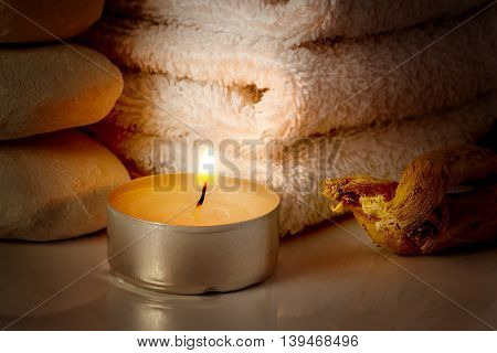 restful image of burning candle on a background of white towels