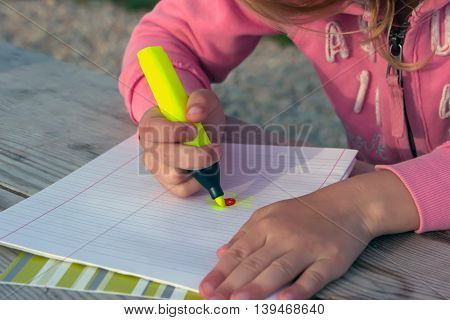 small child of preschool age in the pink dress and blond hair draws sitting at the big wooden table flower is very bright shades of green felt-tip pen