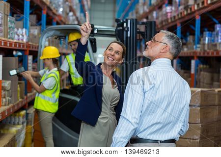 Managers are pointing and looking shelves in a warehouse