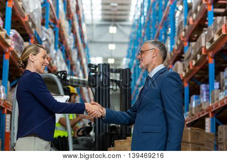 Business people are handshaking and smiling in a warehouse