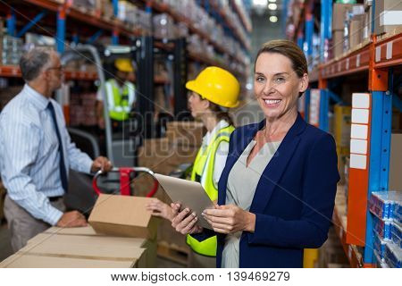 Business woman standing in front warehouse worker in warehouse