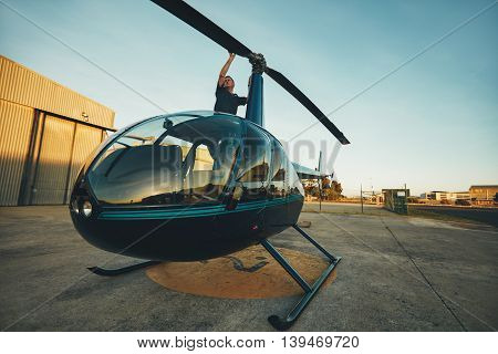 Pilot Inspecting The Rotor Blades Of A Helicopter