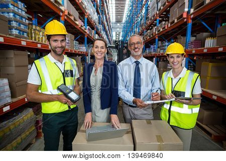Businessmen and warehouse workers in warehouse