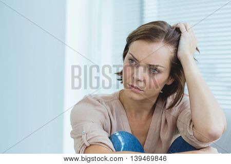 Depressed woman looking away at home