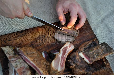 Slicing the cold pork to prepare a picnic meal on a wooden desk