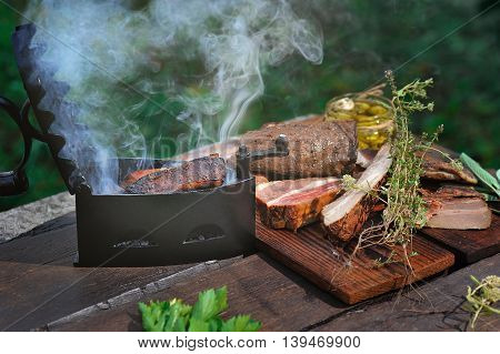 Smoking bacon in a vintage iron used for barbecuing, on a wooden table outdoors