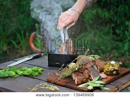Barbecuing pork in a vintage iron, with other kind of meats, thyme, sage and goat cheese on the wooden table