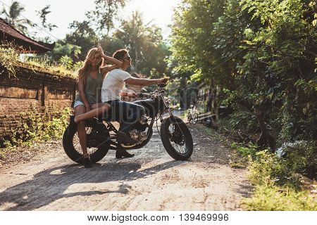 Couple Hanging Out With Motorcycle On Village Road