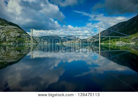 Mountains and bridge reflecting in calm water