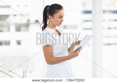 Focused young woman using digital tablet at home