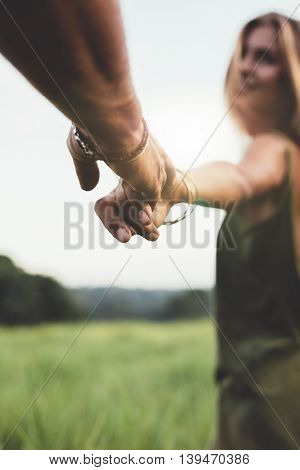 Man Holding Hand Of His Girlfriend In Grass Field