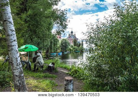Pereslavl Zalessky, Russia - July 21, 2016: The unknown painter in leather boots and with a black cat on hemp draws an imperceptible tree on other river bank though directly before him a wonderful landscape.