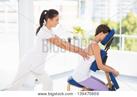 Woman being massaged on chair by masseuse at spa