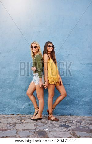 Full length image of two young female friends standing back to back against blue wall and looking at camera. trendy young women in stylish outfits.