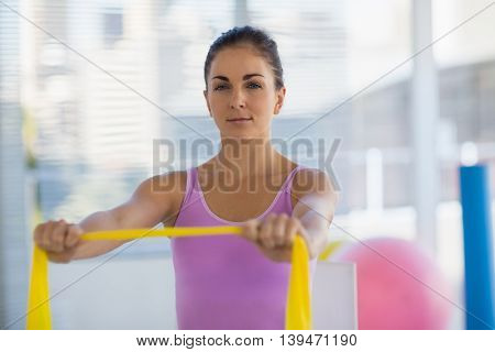 Portrait of woman holding resistance band at fitness studio