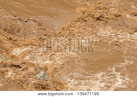 Closeup of rapid flow of brown water in the muddy river during rainy season