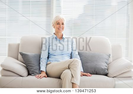 Portrait of smiling senior woman sitting on sofa at home