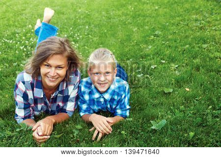 Happy mother and child laying on meadow