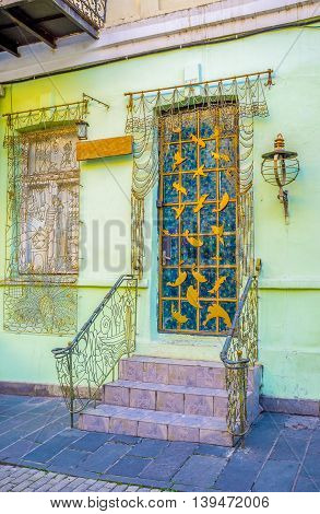 The house entrance and the window decorated with the curtains and tulle made of the metal wire Tbilisi Georgia.