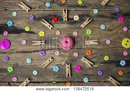 Accessories for needlework multi color botton and clothes peg on old wooden background