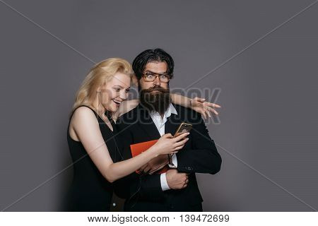 Surprised couple of young blond woman in black dress and handsome bearded hipster man in suit glasses with folder look in smartphone on grey wall