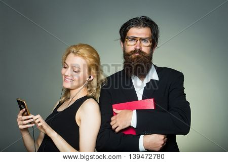 Elegant couple of smiling young woman in black dress listens to music in smartphone with earphones and handsome bearded hipster man in glasses suit keeps folder on grey wall