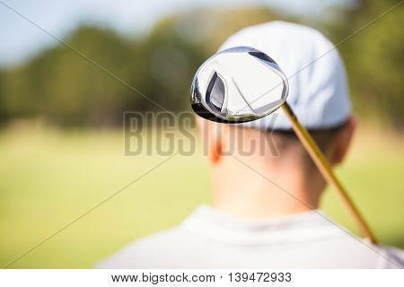 Focus on foreground of golf club behind the neck of golfer