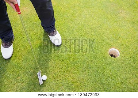 Low section of man playing golf while standing on field