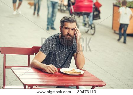 handsome sexy bearded young man hipster with long beard and mustache on serious hairy face sitting at cafe red table with pizza on plate outdoor