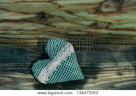 Green soft heart of checkered fabric with white lace decoration on wooden background