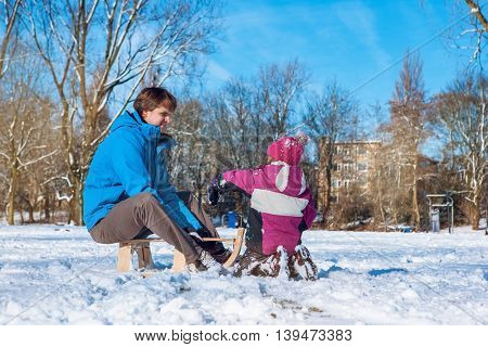 Father and child playing with snow in a winter park
