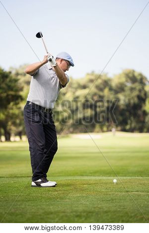 Profile view of man playing golf while standing on field