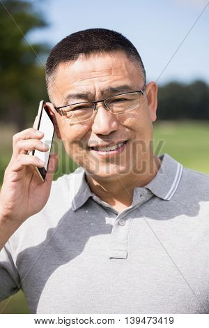 Portrait of golfer smiling and calling with his mobile phone