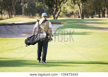 Rear view of sportsman walking with his golf bag on a field