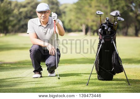 Golfer crouching and posing on field