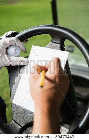 Close up of hand filling a piece of paper in a golf buggy