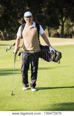 Sportsman posing with his golf bag on a field