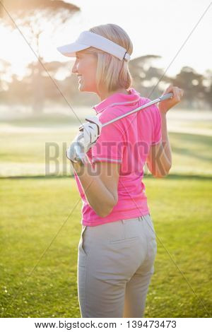 Side view of woman golfer holding her club on field