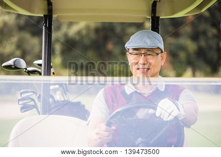 Golfer driving a golf buggy on a field