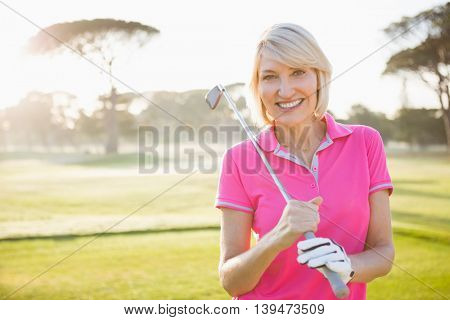 Woman posing with her golf club on field