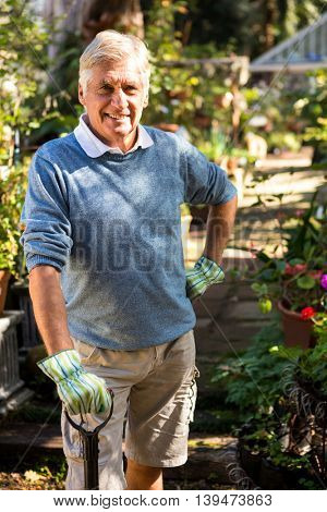 Portrait of happy gardener with shovel while hand on hip at garden