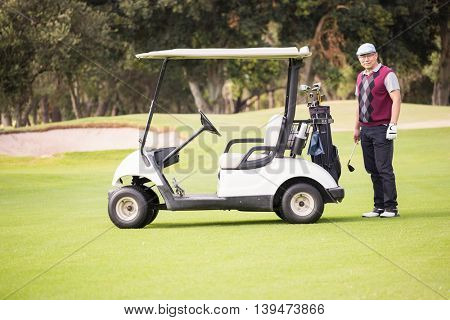 Golfer posing next to his golf buggy on a field