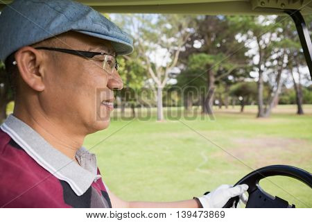 Golfer driving golf buggy on the golf course