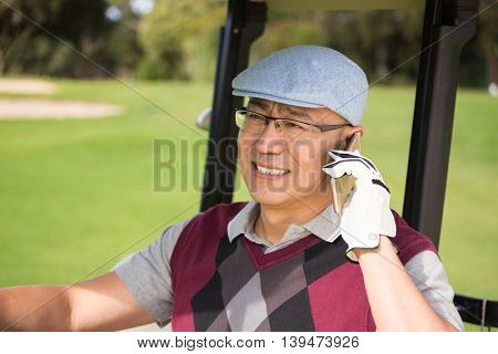 Golfer smiling and calling in his golf buggy