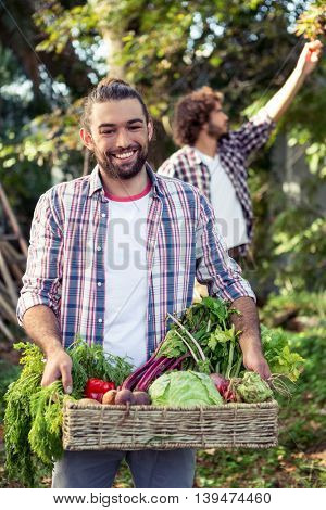 Portrait of happy young gardener with vegetables at garden