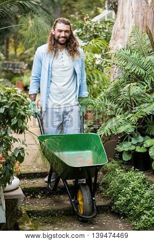 Portrait of happy young male gardener pushing wheelbarrow at garden