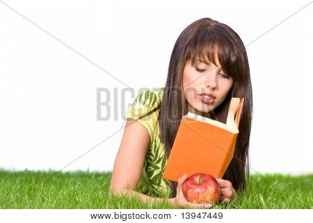 young woman reading book on grass. white background
