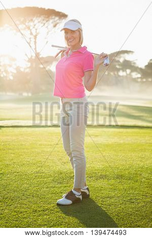 Woman golfer posing with her golf club on field