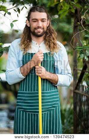 Portrait of happy young male gardener holding work tool at community garden